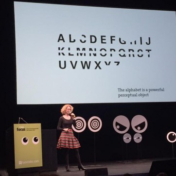 ellen lupton on stage at TYPO SF with struckout text behind her